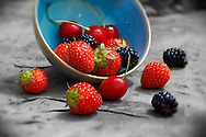 A bowl of fresh picked, strawberries, blackerries and cherries