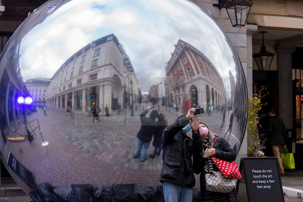 """© Licensed to London News Pictures. 23/10/2020. LONDON, UK. Passers by interact with a new reflective sculpture called """"A~V"""", 2020, by Ben Cullen Williams in Covent Garden.  Shaftesbury, owner of 16 acres of land in the capital including Chinatown, parts of Soho and Covent Garden, has announced emergency plans to raise almost £300m to help it survive the coronavirus pandemic as tourists and workers stay away from the West End. The property firm is struggling to collect rent from its retail, restaurant and bar tenants, who have had persistently lower footfall and trade.  Photo credit: Stephen Chung/LNP"""