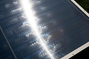 A close-up of sun reflecting off  a solar thermal panel. Solar water heating systems use heat from the sun to work alongside your conventional water heater