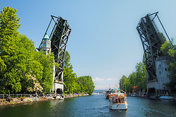 United States, Washington, Seattle. Boats pass through the Mountlake Cut between Lake Union and Lake Washington, under the Mountlake drawbridge. Opening Day of Boating Season