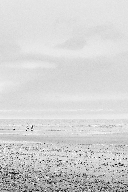 Looking out to sea, a lady and gentleman walk their dog across the beach along the water line.<br /> <br /> Photo by Jonathan J Fussell, COPYRIGHT 2021