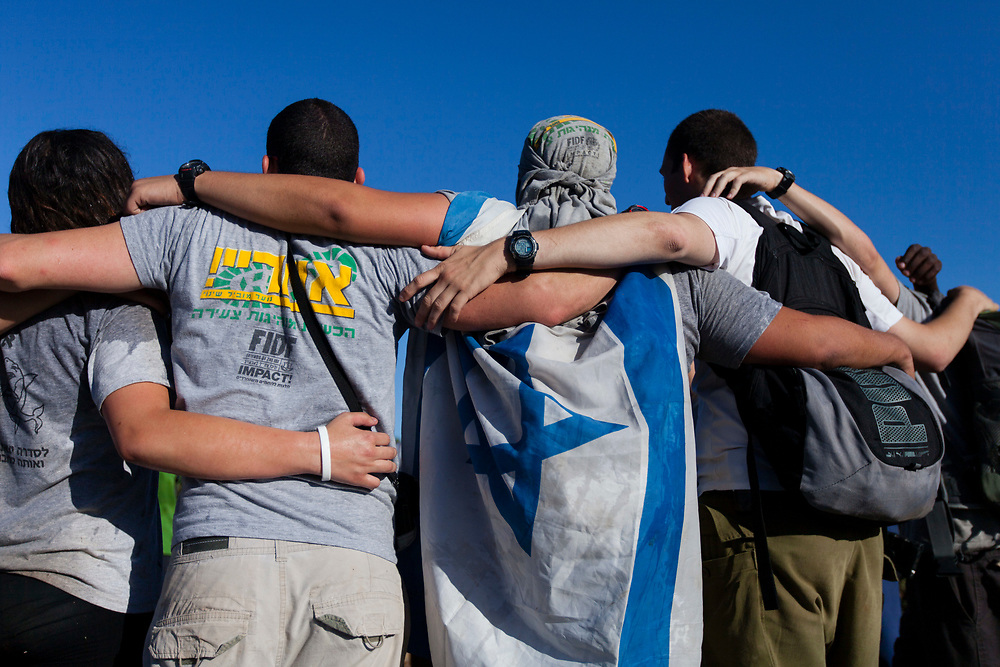 Israeli youths participating in 'Aharai! Youth Program' embrace each other as they complete the program's final stage, an overnight stretcher march to Mount Herzl in Jerusalem, Israel, on June 28, 2013, where they took part in a ceremony marking 15 years since the foundation of the Aharai! Youth Program. 'Aharai!' is a social educational organization that develops young leadership and promotes social involvement among youths from underprivileged communities, including boarding schools, immigrant and absorption centers, welfare services, boarding schools, shelters and criminal rehabilitation programs, by connecting the youths to milestones in Israeli society: preparation for a significant military service in the IDF, preparation for the matriculation exams, immigrant integration programs, youth challenge programs, one year of community service, pre-military academy and alumni organization. The organization provides its youths a sense of achievement and capability and encourages them to fit in as contributing citizens in the State of Israel.