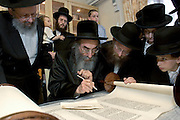 A new Sefer Torah being completed by the Alexandria Rebbe before being paraded to synagogue. Members of the congregation and spiritual leaders help the scribe finish off the Torah before it goes Kehal Chareidim Beth Hamedrash, an Ashkenazi synagogue in Stamford Hill.