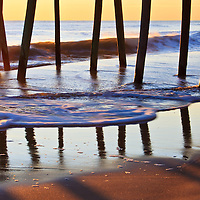 Reflections, shadows, and silhoutte of the fishing pier against sunrise and ocean waves, Virginia Beach, Virginia.