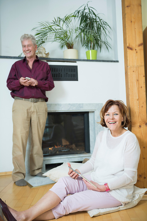 Portrait of seniorcouple sitting in front of fireplace with smart phone and digital tablet, smiling