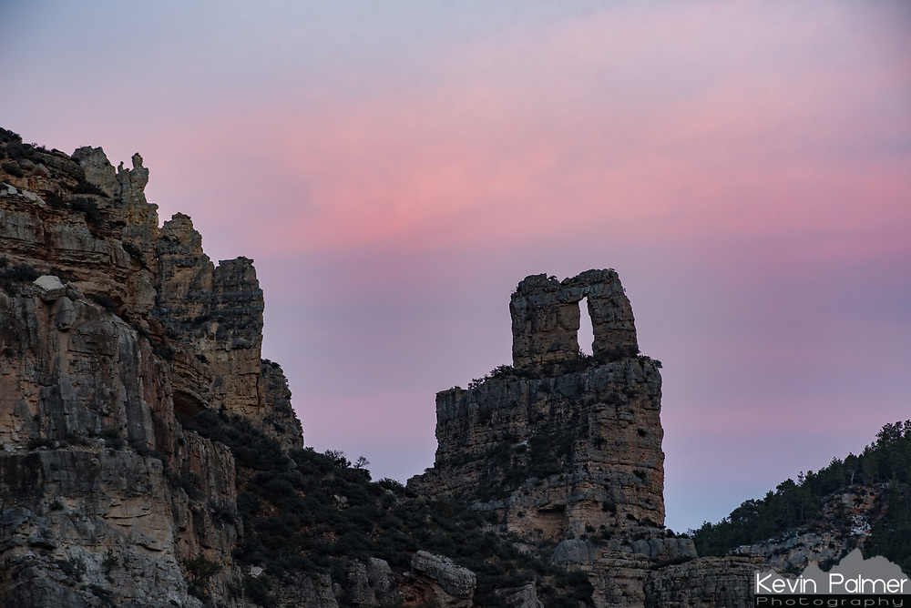 The Needle's Eye or Keyhole Arch stands above the entrance to Tongue River Canyon. The thin lingering clouds behind it lit up with a soft pink glow after sunset.