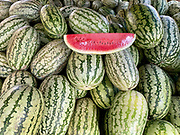Pile of watermelons in a market with one sliced open to show the quality of the melons