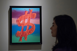 """© Licensed to London News Pictures. 29/06/2017. London, UK.  A woman views """"Dollar Sign"""", 1981, by Andy Warhol.  Members of the public visit Masterpiece London, a leading art fair held in the grounds of the Royal Hospital Chelsea.  The fair brings together 150 international exhibitors presenting works from antiquity to the present day and runs 29 June to 5 July 2017.  Photo credit : Stephen Chung/LNP"""