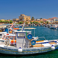 Colourful fishing boats in the harbour with the elegant 19th century Neo Classical Vogiatsis Mansion in the background. Aegina, Greece.