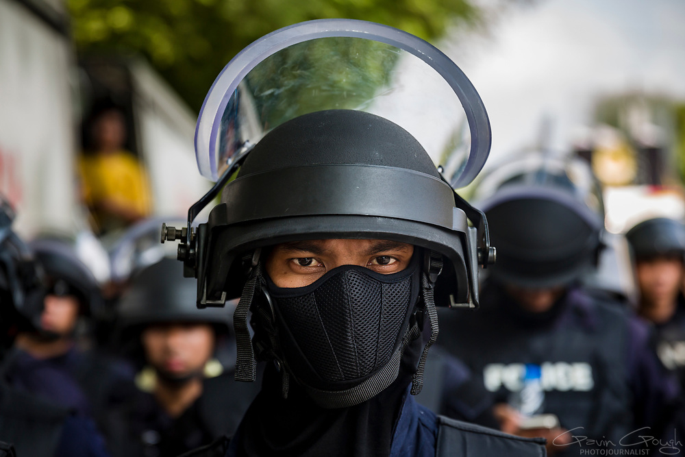 A policeman wearing protective clothing standing in a line of police facing anti-government protesters in Bangkok.