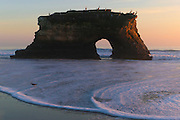 Pacific Ocean waves crash up against the one remaining arch in Natural Bridges State Park in Santa Cruz, California. There used to be three arches. Arches form when waves continually pound a weak spot in the rock, wearing a hole through it. Over time, continued erosion enlarges the hole so much that the overlying rock can no longer be supported and the arch collapses.