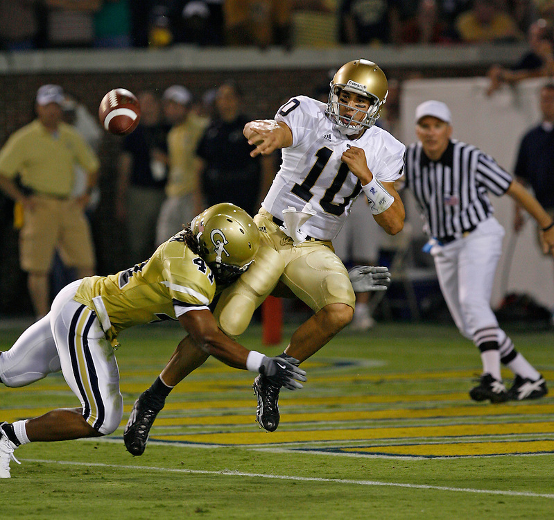 Notre Dame QB Brady Quinn lets go off a pass after being hit by Georgia Tech LB Philip Wheeler during the game at Grant Field at Bobby Dodd Stadium in Atlanta, GA on September 2, 2006.