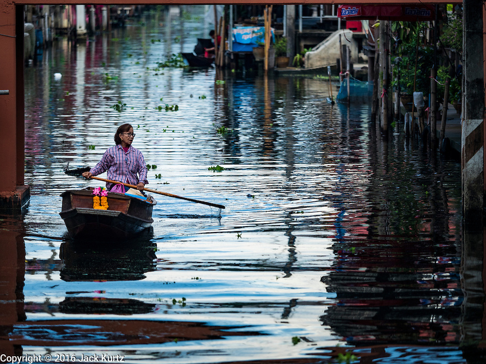 27 SEPTEMBER 2016 - BANGKOK, THAILAND:  A woman paddles her canoe through the khlong (canal) at the floating market in Damnoen Saduak, Thailand. The market is famous because vendors cruise the canals around the market selling produce and tourist curios. It is one of the best known tourist attractions in Samut Songkhram province.     PHOTO BY JACK KURTZ