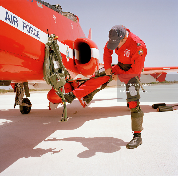 Flight Lieutenant Dan Simmons of the elite 'Red Arrows', Britain's prestigious Royal Air Force aerobatic team, zips up his g-pants before climbing into his Hawk jet. G-pants counterac the effects of high gravity stresses that jet-fighters impose on the human body, automatically inflating and squeezing blood back to the thorax and head when blood drains towards the legs. As he attaches the zipper, he rests his straight right leg on a retractable step which helps him and his ground crew engineers to gain access to the cockpit, high above the ground. Hanging from another part of his airplane is his life-vest which he will wear around his neck, whilst in flight. Flight Lieutenant Simmons wears heavy-duty black boots which are regulation footwear for flying personnel and dressed in his red flying suit that is famous around the world.
