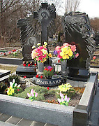 Dressed to kill: Gaudy tombstones of Russian gangsters depict them wearing designer suits with flash cars<br /> <br /> <br /> They used to spend their days collecting protection money, kneecapping those who would not pay up and planting explosives in the cars of their rivals.<br /> But now the only reminders of the gangsters that made up the Russian mobs in the 1990s are their tombstones with gaudy sketches of them etched into the granite. <br /> The men, who are casualties of the Russian business world and were relatively young when they were killed, are sculpted standing in designer suits and leather jackets.<br /> hey stare back at the onlooker, smiling or stern, as proud in death as when they were alive.<br /> Their graves are marked by life size headstones, where their images are expertly engraved into imported marble.<br /> On the edge of the Russian city of Yekaterinburg lies the Shirokorechenskoye cemetery.<br /> This is the final resting place for mobster, Miklhail Kuchin, boss of the notorious Centralnaya gang who was gunned down aged 35 as he left his home. <br /> His gravestone shows him as thick-necked, dressed in a double breasted suit. and he is depicted clutching the keys to his beloved Mercedes 600.<br /> This, in a country where buying a Lada is beyond millions of people's pockets, working or not.<br /> Nearby are the graves of father and son gangsters Nikolai and Andrei Kravtsov, shot by contract killers as they drove in their Volvo in 1996. They were cut down at the ages of 44 and 22.<br /> Hefty gravestones commemorate the two men and between them a separate stone is dedicated to their precious car.<br /> On their tombs, some are depicted with their tattoos, or smoking cigarettes. <br /> Others are buried with their mobile phones so they can be kept up to date with the daily round of gangland shootings and beatings.<br /> In an enormous tomb-Oleg Vagin is buried alongside his three armed bodyguards, who couldn't draw their guns fast enough to sa