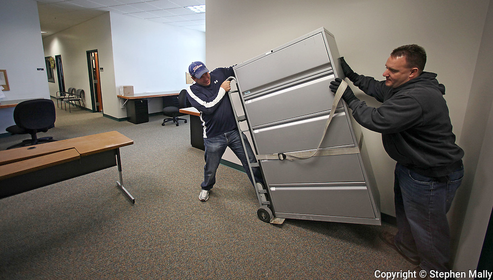 Major Doug Riniker (from left) and Sergeant Deric Oshel set down a file cabinet at the Linn County Sheriff's Office in Cedar Rapids on Friday January 8, 2010. (Stephen Mally/Freelance)