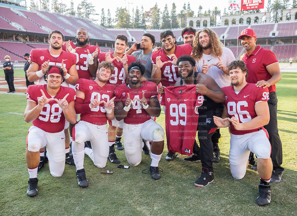 PALO ALTO, CA - OCTOBER 2:  The Stanford Cardinal defensive line poses on the field after Stanford's 31-24 overtime victory over the Oregon Ducks in a Pac-12 college football game on October 2, 2021 at Stanford Stadium in Palo Alto, California; (L-R, front row) Zack Buckey #98, Trey LaBounty #93, Thomas Booker #4, Zephron Lester #99, Jacob Katona #96 (L-R back row)  Matthew Merritt #55, Ryan Johnson #23, Anthony Franklin #94, Aristotle Taylor (grey tshirt), Tobin Phillips #40, Aaron Armitage #97 (red headband),  Tucker Fisk (white tshirt), Defensive Line Coach Diron Reynolds.  (Photo by David Madison/Getty Images)