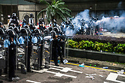 Police fire tear gas at protesters occupying roads in front of the Central Government Offices, during a protest against a proposed extradition law in Hong Kong, SAR China, on Wednesday, June 12, 2019. Hong Kong's legislative chief postponed the debate on legislation that would allow extraditions to China after thousands of protesters converged outside the chamber demanding the government to withdraw the bill. Photo by Suzanne Lee/PANOS