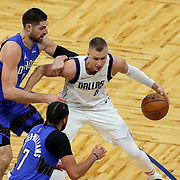 ORLANDO, FL - MARCH 01: Kristaps Porzingis #6 of the Dallas Mavericks controls the ball in front of Nikola Vucevic #9 of the Orlando Magic and Michael Carter-Williams #7 of the Orlando Magic during the second half at Amway Center on March 1, 2021 in Orlando, Florida. NOTE TO USER: User expressly acknowledges and agrees that, by downloading and or using this photograph, User is consenting to the terms and conditions of the Getty Images License Agreement. (Photo by Alex Menendez/Getty Images)*** Local Caption *** Kristaps Porzingis; Nikola Vucevic; Michael Carter-Williams