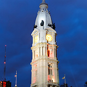 The tower of Philadelphia's City Hal at night against a cloudy sky.