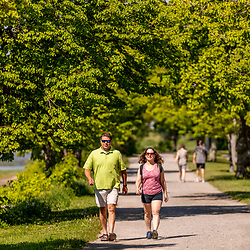 A man and woman walking on the Back Cove Trail next to Back Cove in Portland, Maine.