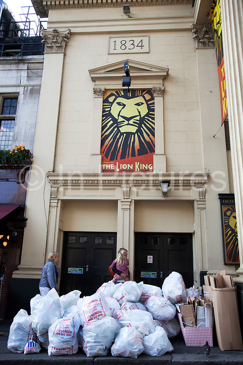 Rubbish piled up in bags outside the Lyceum Theatre in the West End of London, UK. In this part of town it is a comon sight to see enormous piles of waste sitting, waiting to be collected, and is unsightly in an are where tourism is rife.
