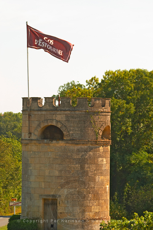 A tower in the vineyard at Chateau Cos d'Estournel with a flag with the name of the Chateau