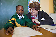 A young African school girl shares a joke with her volunteer literacy teacher during a reading session in a classroom in Observatory Primary School, Cape Town, South Africa. The volunteer teachers have been provided to the school by Shine Centre which is a charity that aims to address the high illiteracy rate in South Africa by improving literacy levels among children in schools and disadvantaged communities.