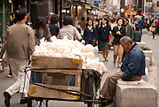 An elderly Korean man with a hand-cart selling bags of rice-based dried snack products in Insadong a major arts and crafts, and tourist district in Seoul.