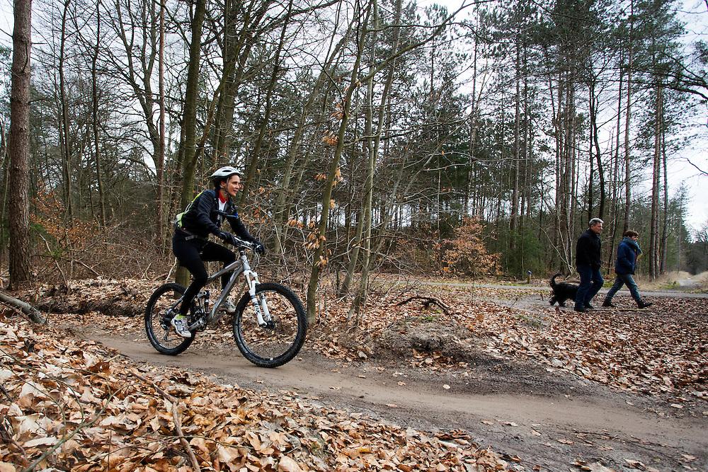 Bij Zeist fietsen mountainbikers over het speciaal aangelegde mountainbike parcours. Twee wandelaars lopen met hun hond op het naastgelegend wandelpad.<br /> <br /> Mountainbike riders at the special track near Zeist. Two hikers walk at the nearby hiking path with their dog.