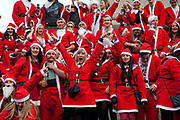 London, UK. Sunday 9th December 2012. A flash mob of Santas descends on Trafalgar Square, climbing up to sing festive songs. Christmas celebrated here with the annual Santa Pub Crawl party visiting the famous pubs & sights of London with everyone decked out in jolly red Santa suits. Organised by Fanatics, an Australian sports and party company.