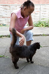 Young woman stroking a cat,