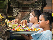 11 OCTOBER 2016 - UBUD, BALI, INDONESIA: Women pray at the Hindu temple in the market in Ubud. The temple in the market is very busy during the midmorning hours, when market vendors come to pray. The morning market in Ubud is for produce and meat and serves local people from about 4:30 AM until about 7:30 AM. As the morning progresses the local vendors pack up and leave and vendors selling tourist curios move in. By about 8:30 AM the market is mostly a tourist market selling curios to tourists. Ubud is Bali's art and cultural center.      PHOTO BY JACK KURTZ