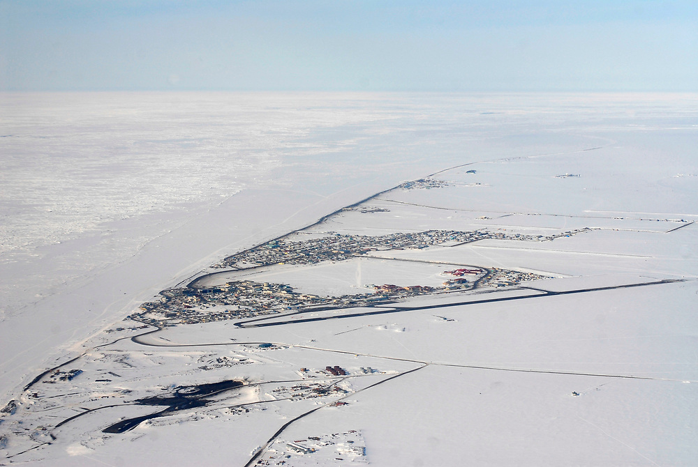 Alaska, Barrow. Aerial view of frozen ocean and lead and the village of Barrow. Spring 2007