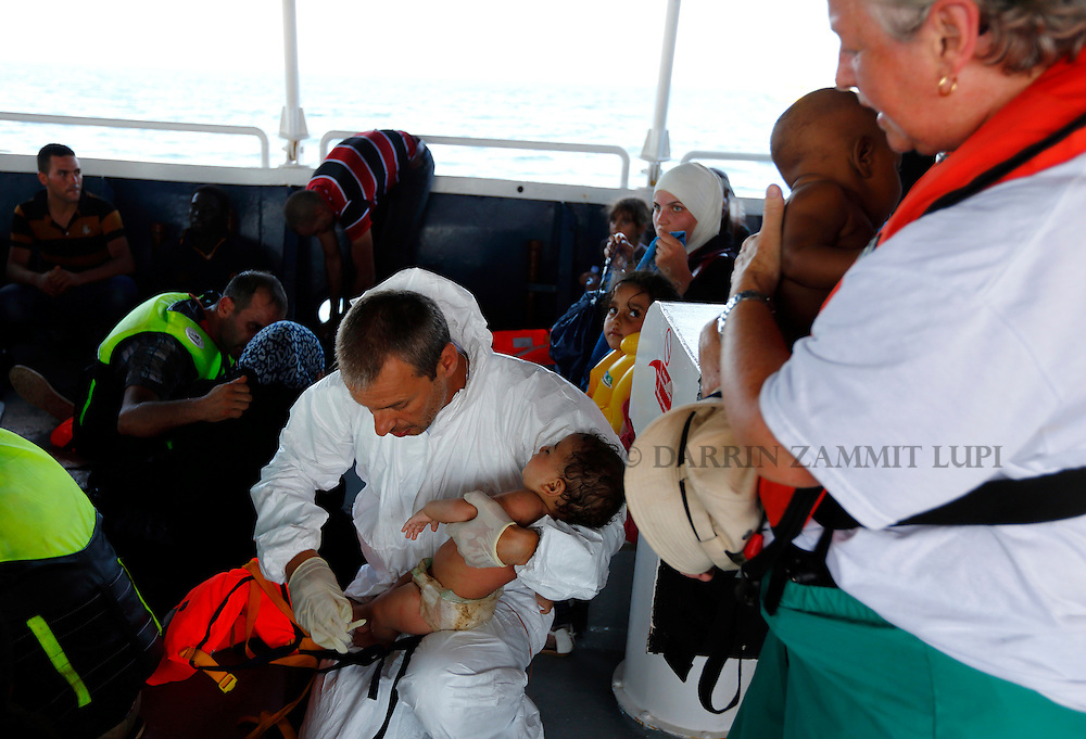 Crew members carry migrant babies on Migrant Offshore Aid Station (MOAS) ship MV Phoenix after they were rescued from an overloaded wooden boat off the coast of Libya August 6, 2015.  An estimated 600 migrants on the boat were rescued by the international non-governmental organisations Medecins san Frontiere (MSF) and MOAS without loss of life on Thursday afternoon, a day after more than 200 migrants are feared to have drowned in the latest Mediterranean boat tragedy after rescuers saved over 370 people from a capsized boat thought to be carrying 600.<br /> REUTERS/Darrin Zammit Lupi <br /> MALTA OUT. NO COMMERCIAL OR EDITORIAL SALES IN MALTA