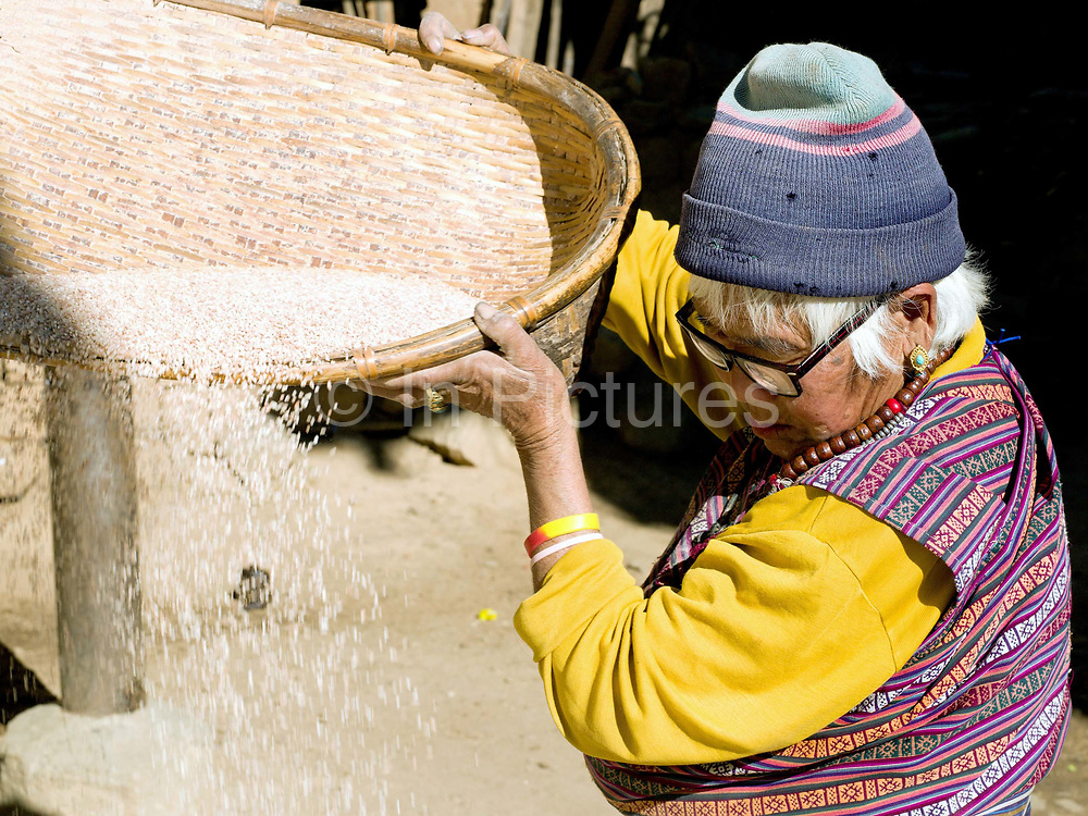 A farmer wearing a handwoven kira, the Bhutanese national dress, prepares rice for cooking outside her home in Richengang village near Wangdue, Western Bhutan. Despite rapid urbanisation, the majority of people, 66% of all households, still live in rural Bhutan, most dependent on the cultivation of crops and livestock breeding.