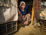 07 NOVEMBER 2014 - SITTWE, RAKHINE, MYANMAR: SATA RA, 25, a Rohingya Muslim woman, in the doorway of her home. After sectarian violence devastated Rohingya communities and left hundreds of Rohingya dead in 2012, the government of Myanmar forced more than 140,000 Rohingya Muslims who used to live in and around Sittwe, Myanmar, into squalid Internal Displaced Persons camps. The government says the Rohingya are not Burmese citizens, that they are illegal immigrants from Bangladesh. The Bangladesh government says the Rohingya are Burmese and the Rohingya insist that they have lived in Burma for generations. The camps are about 20 minutes from Sittwe but the Rohingya who live in the camps are not allowed to leave without government permission. They are not allowed to work outside the camps, they are not allowed to go to Sittwe to use the hospital, go to school or do business. The camps have no electricity. Water is delivered through community wells. There are small schools funded by NOGs in the camps and a few private clinics but medical care is costly and not reliable.   PHOTO BY JACK KURTZ