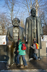 Children climbing on bronze statues of Marx and Engels in Alexanderplatz Mitte  Berlin Germany