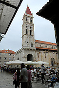 Tower of Cathedral of Saint Lawrence (Katedrala sveti Lovre), with cafe chairs, tables and umbrellas in foreground. Trogir, Croatia.