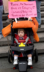 12 Jan, 2006. New Orleans, Louisiana. Post Katrina.<br /> 17 month old Joseph Sanders sits in his buggy as part of the protest at the lack of effective levees in New Orleans as President George Bush comes to town. <br /> Photo; Charlie Varley/varleypix.com