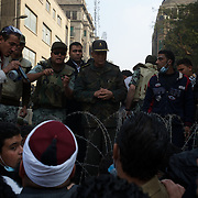 An egyptian army official talks with a group of protestors near a Ministry building in central Cairo.