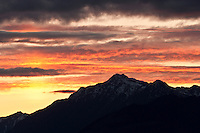 Mount Jupiter silhouetted against a post sunset sky with alpenglow painted clouds seen from the Kitsap Peninsula in Puget Sound, Washington state, USA.