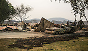 Burned-out trucks and a mobile home along Johnson Creek Road, north west of Omak as wildfires burn central Washington August 20, 2015.<br /> <br /> Bettina Hansen / The Seattle Times