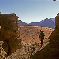 Rakabat Siq, Jebel Um Ishrin, Wadi Rum, Jordan. A rock climber hikes between remote desert cliffs in Rakabat Siq (canyon), on (Mount) Jebel Um Ishrin, Wadi Rum, Jordan.