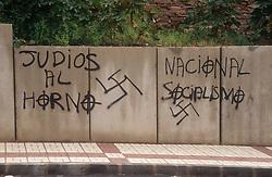 Racist fascist graffiti sprayed on stone wall,