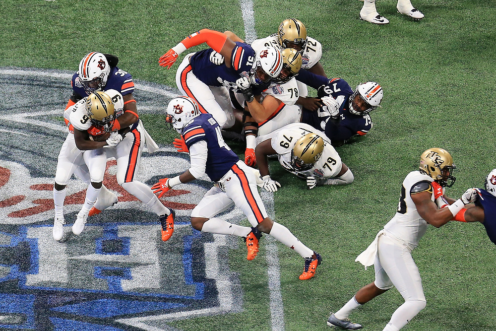 UCF Knights running back Adrian Killins Jr. (9) is tackled by Auburn Tigers linebacker Tre' Williams (30) during the 2018 Chick-fil-A Peach Bowl NCAA football game on Monday, January 1, 2018 in Atlanta. (Daniel Shirey / Abell Images for the Chick-fil-A Peach Bowl)
