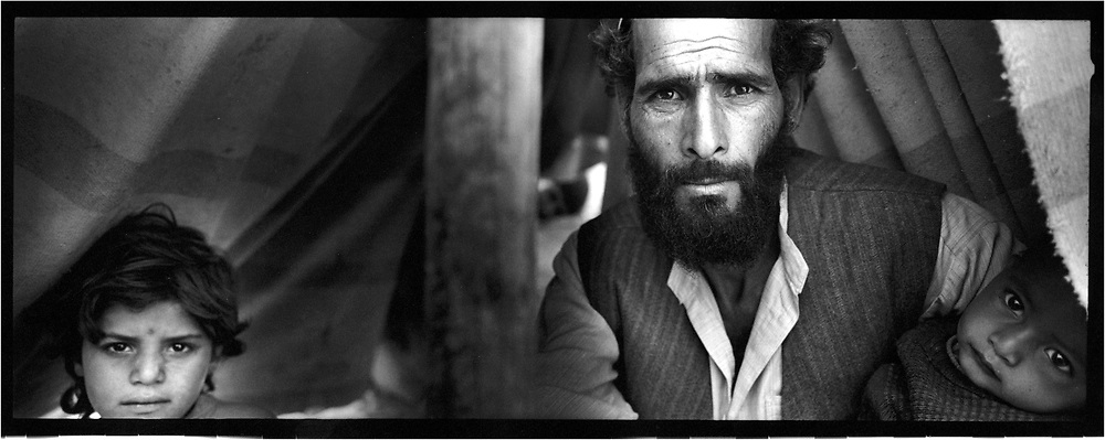 Afghanistan. Jalallabad. A few days after the fall of talibans, the capital is quiet. The people doesn't seem to believe what happened or maybe they became so careful with their terrible destiny. A man poses under a shelter near Jalallabad with his children. His wife stay away of the foreigners.