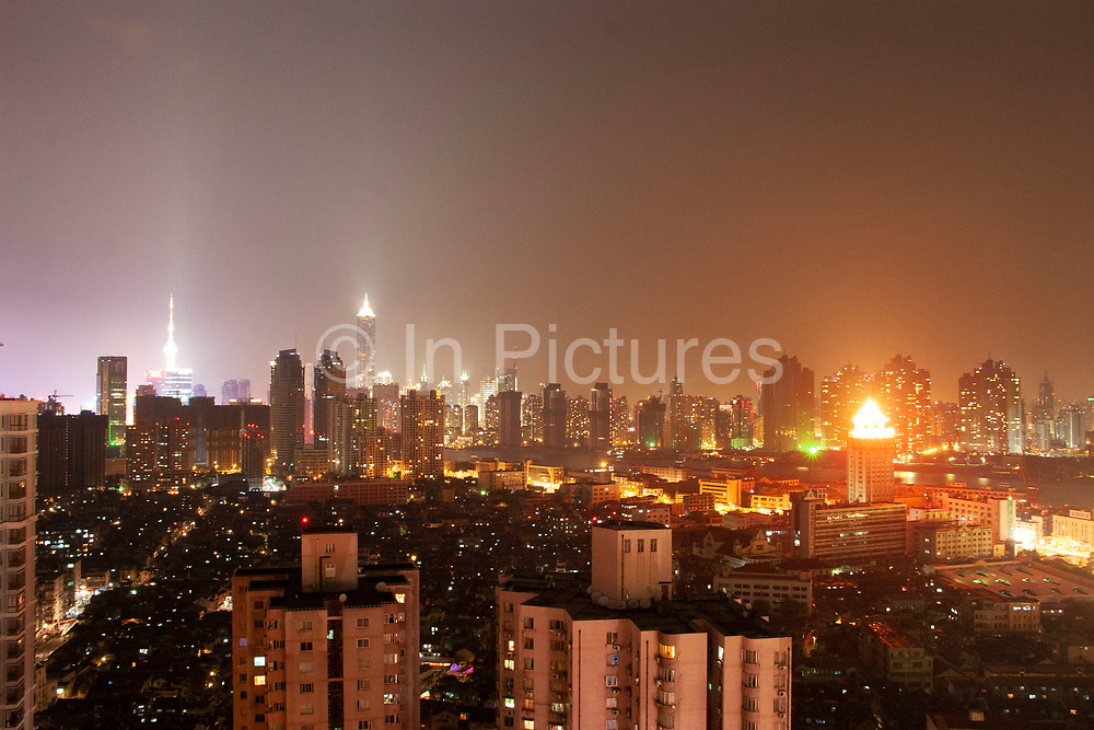 The Oriental Pearl Tower left and Jin Mao Building right rise up, glowing in the distance in Pudong, and China's centralised financial district in Shanghai, China. Skyline across the low-rise traditional Chinese housing in the foreground of Nanpudaqiao through the high-rise developments, offices and apartment buildings right across downtown, this vision of capitalism and modernity against traditional sums up the colossal development of this 'Paris of the East' as Shanghai was once known. In ten years the city has gone from 2-3 story housing as far as the eye can see to this rising metropolis. So much air pollution and light pollution from buildings, construction, cars and lighting up makes the whole city glow.