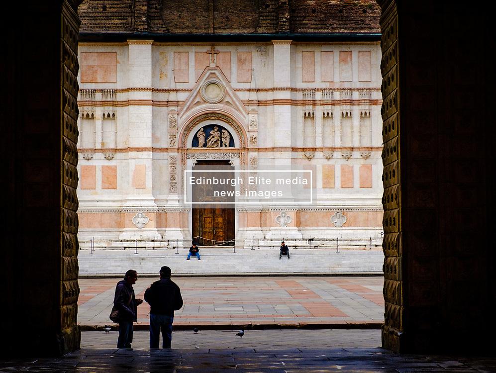 Two men chat in the Piazza Maggiore with the Basilica di San Petronio in the background, Bologna, Italy<br /> <br /> (c) Andrew Wilson | Edinburgh Elite media