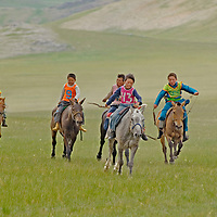 Young, costumed bareback riders approach end of a 20km race at a traditional naadam festival on a remote pass in Arbulag Sum, near Muren in Hovsgol Aimag, Mongolia.